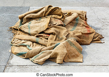 Close up old and dirty sacks on concrete floor