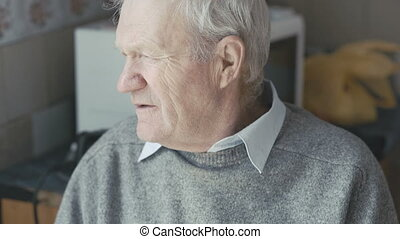 Old sad grandfather looking at the window and camera 4K
