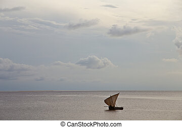 old sailing boat in the ocean at sunset