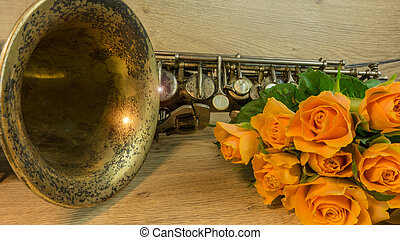 Old saxophone with roses on a wooden table
