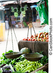 Old scales on open market with vegetables on shelves. Selective focus on the scales.