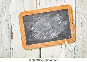Old school blackboard with chalk on a wooden background