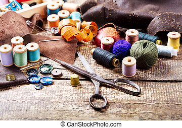 old scissors, various threads and sewing tools on wooden...