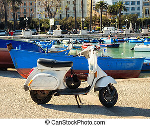 Old scooter near fishing boats in Bari, Italy.
