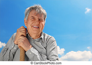 old senior in striped shirt with shove smiling and looking...