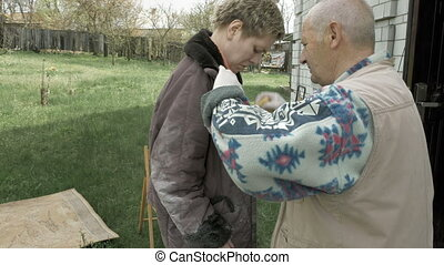 Old senior man helps young woman to clean clothes