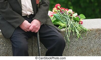 Old senior veteran with cane and flowers. Close up. Veteran...