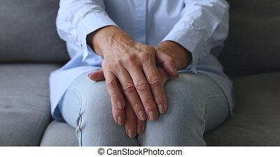 Old senior woman sit on sofa with hands folded, closeup - ...
