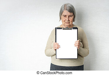 Old senior woman with empty white paper as a blank for copy space