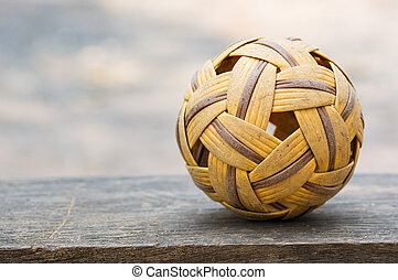 Old Sepak takraw ball put on the wood.