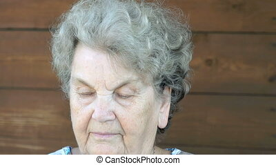 Old serious woman talking on the cell phone