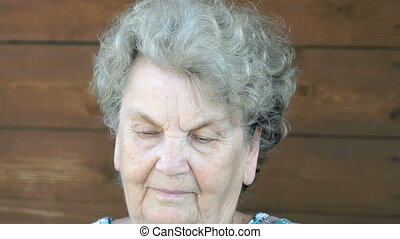 Old serious woman talking on the mobile phone