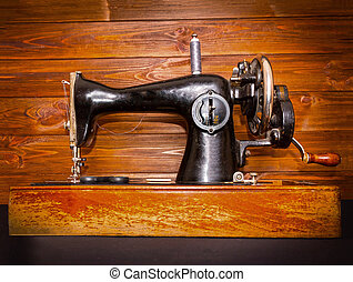 The old sewing machine on wooden background.