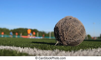 Old shabby ball lies on the football field