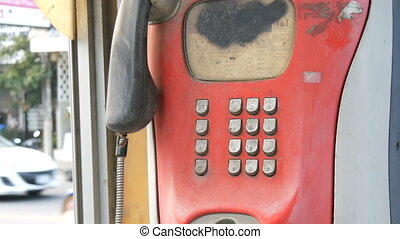 Old shabby red telephone set on a city street. Vintage...