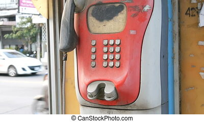 Old shabby red telephone set on a city street. Vintage telephone in the phone booth
