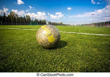 shabby soccer ball lying on artificial grass field