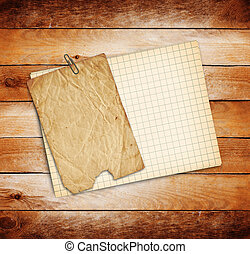 Old sheets of paper on grunge wooden background