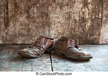Old shoes - Old dirty brown leather shoes on wooden floor.
