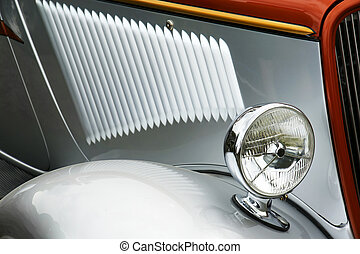 Detail of old silver collectible car, cool light reflections.