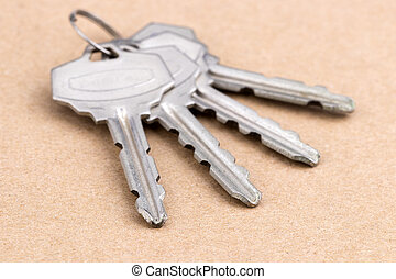 Old silver-color metal keys with key chain on wooden background