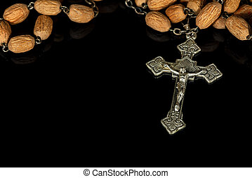 Old silver crucifix with wooden rosary bead on black background