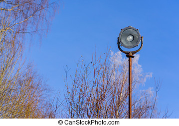 old single street light on a background of blue sky in the forest. vintage