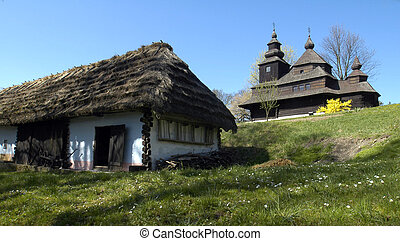 old wooden house with straw roof and well-preserved wooden church in an outdoor museum in city Humenne - east Slovakia;