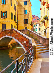 Old small arch bridge over canal in Venice