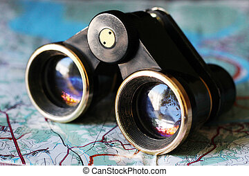 Old small binoculars on the map