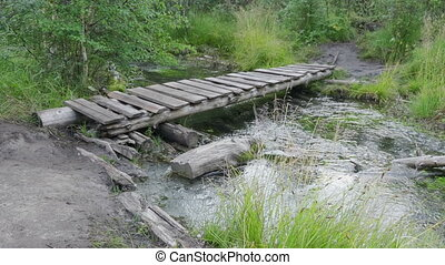 Old small bridge through a river in a forest.