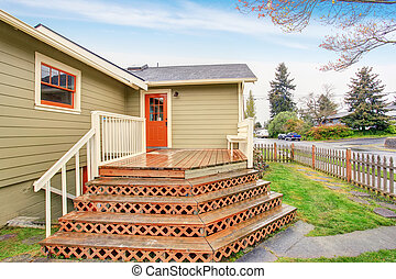 Old small green American home with porch.