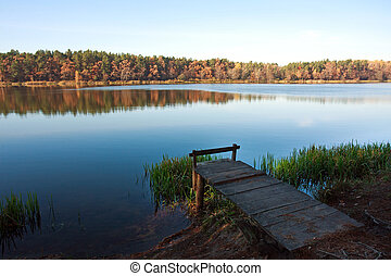 Old small wooden pier for fishing in autumn forest lake