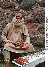 Old smith - Old man in medieval clothes is selling his ...