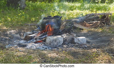 Old smoked teapot on campfire - Old smoked teapot on tourist...