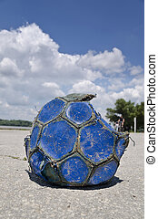 Old soccer ball in the city street