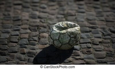 Old soccer ball in the pavement yard