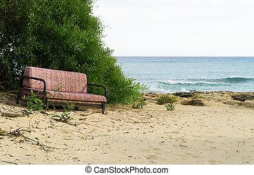 Old sofa on the sea beach.