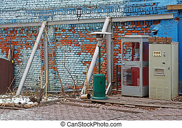 Old soviet telephone booth, soda water machine and gas heater for patio in yard of cafe
