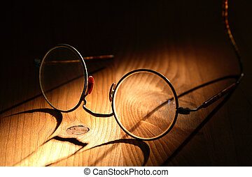 Old Spectacles - Closeup of old spectacles with long shadow...