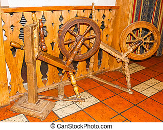 Old spinning wheel on wooden