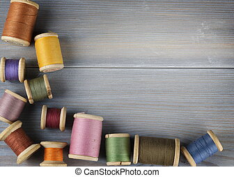 Old spools of thread on wooden background