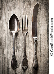 Old spoon, fork and knife on wooden background