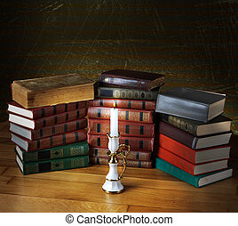 Old stack of books with candlestick and burning candle on...