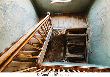 Old staircase in abandoned house filled with sand, Kolmanskop Ghost Town
