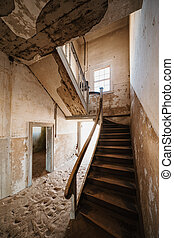 Old staircase in abandoned house filled with sand, Kolmanskop Ghost Town, Namibia