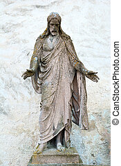 Old statue of Jesus Christ with a grungy wall behind