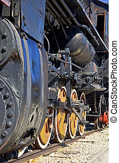 Old steam locomotive in the background of blue sky. Close-up.