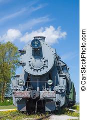Old steam locomotive train under blue sky