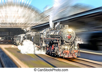 Old steam train locomotive driving past the passenger platform of the station